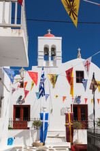 Greek Orthodox Church And Colourful Flags Hanging Over Narrow Alley In Mykonos Town.