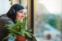Woman Wearing Headphones Looking Through Window During Corona Virus Crisis.