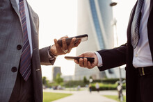 Two Businessmen Wearing Suits Standing Outdoors, Checking Their Mobile Phones.