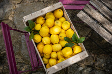 High Angle Close Up Wooden Crate With Freshly Picked Lemons.