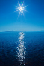 Sun Over Mediterranean Sea With Small Boat And Landmass In The Background.