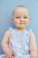 Portrait Of Baby Girl On Pale Blue Background.