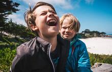 Two Boys Sitting By Sandy Beach Near Carmel, California, USA, Teasing Each Other.