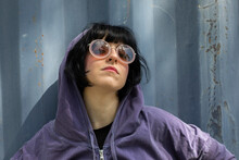 Portrait Of Woman In Hoodie And Round Sunglasses, Looking Defiantly At Camera.