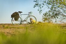 Woman Lying On Ground Next To A Bicycle, Taking A Break During A Cycle Tour Through Canada.