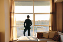 Businessman Looking Out Of Hotel Bedroom Window