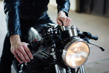Young Male Motorcyclist Straddling Vintage Motorcycle In Garage, Cropped
