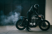 Young Male Motorcyclist Revving Vintage Motorcycle In Garage
