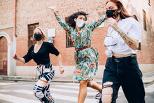 Three Young Women Wearing Face Masks During Corona Virus, Running Across A Pedestrian Crossing In A Street.