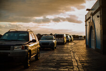 Row Of Parked Cars On A Cobbled Promenade At Dusk, Cloudy Sky.