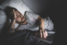 Bearded Young Man Lying In Bed At Night, Looking At Laptop.