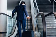 Businessman With Wheeled Luggage On Hotel Escalator