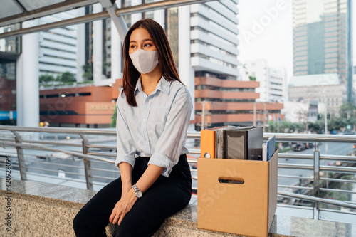 Obraz Stressed and worried young Asian woman with box of items sitting alone after being laid off from job due to covid-19 pandemic - fototapety do salonu