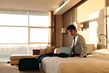 Businessman Using Laptop On Bed Of Hotel Bedroom