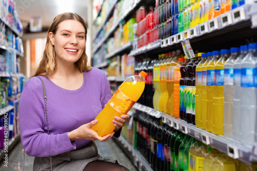 Fototapeta Portrait of young happy glad cheerful positive smiling woman satisfied with choosed carbonated soft drinks in food store obraz