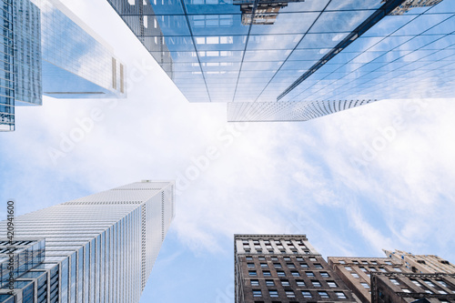City skyscrapers bottom view against blue sky. Low wide angle shot, from ground. Modern business district concept, 3d render. Copy space