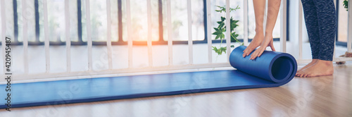Foto Banner Woman hands rolled up yoga mat on gym floor in yoga fitness training room