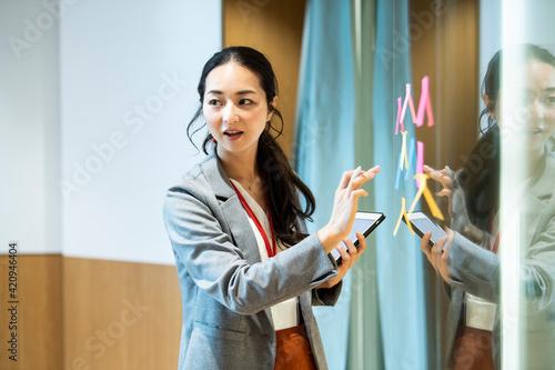 Fototapeta 付箋にアイディアを出し会議を進行する女性社員