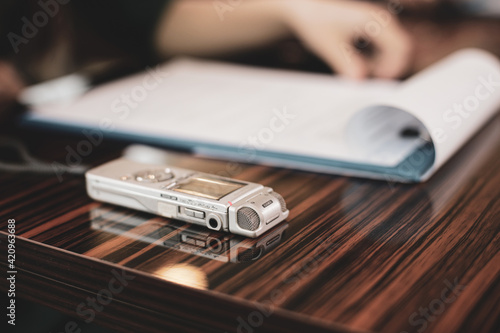 Fotografia Shallow depth of field (selective focus) image with an audio recorder of a woman journalist during an interview