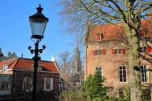 Tinnenburg House (on The Right Side), An Impressive Historic Building (dated From 1414) Located Along Muurhuizen Street In Amersfoort, Utrecht, Netherlands, With Onze Lieve Vrouwe Toren