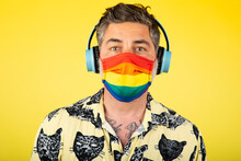 Portrait Of Happy Man With Headphones And Gay Pride Mask On A Yellow Background