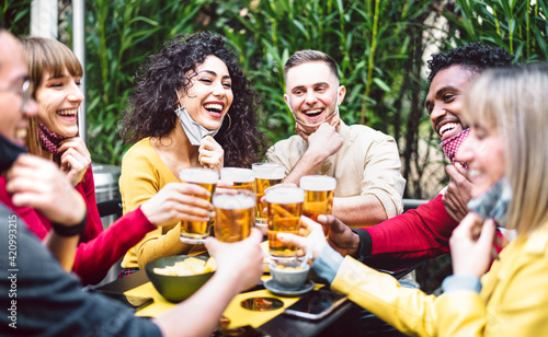 Young people toasting beer wearing open face mask - New normal life style concept with friends having fun together outside at brewery bar garden - Warm filter with focus on woman in yellow clothes - fototapety na wymiar