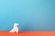 white color origami pigeon on orange table and blue background