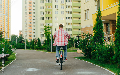 Fototapeta Back of a young man walks on a city bike in the evening in the yard. An adult man in casual clothes rides a bicycle in the yard. Eco transport obraz