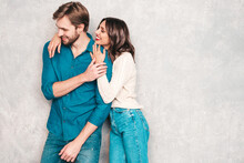 Smiling Beautiful Woman And Her Handsome Boyfriend. Happy Cheerful Family Having Tender Moments Near Grey Wall In Studio.Pure Cheerful Models Hugging.Embracing Each Other