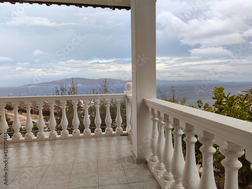 Fotografia View from traditional Greek architecture white terrace balcony with balusters on stormy epic cloudscape and Aegean sea