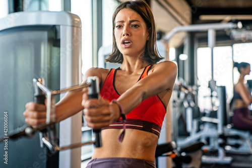 Leinwand Poster Young fitness woman exercising in a gym