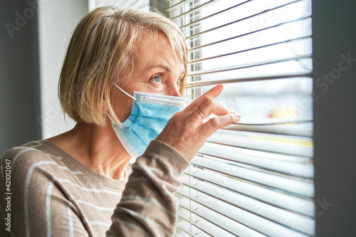 Obraz Quarantined senior woman wearing mask looks through blinds - fototapety do salonu