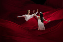 Light. Young And Graceful Ballet Dancers On Red Cloth Background In Classic Action. Art, Motion, Action, Flexibility, Inspiration Concept. Flexible Caucasian Couple With Billowing Red Waves.