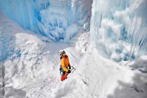 Obraz na plátně Woman climbing frozen waterfall in the mountains