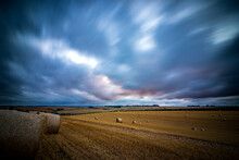 Storm Over Field Of Hay Bales