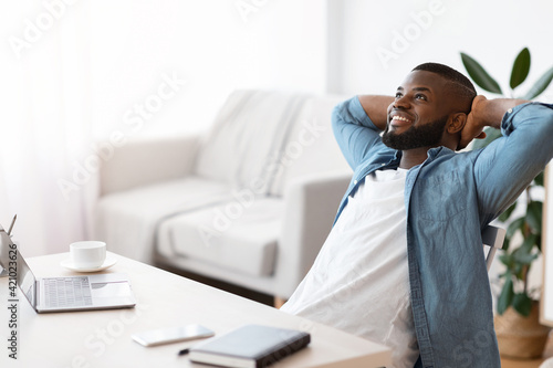 Remote Career. Cheerful African Freelancer Guy Leaning Back In Chair At Home