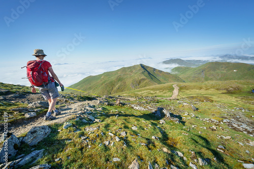 A female hiker descending a mountain path from the summit of Ben Lawers towards Beinn Ghlas with a cloud inversion to the left covering Loch Tay in the Scottish Highlands, UK landscape Fotobehang