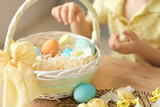unrecognizable little boy puts colored eggs in a wicker Easter basket. easter preparation concept