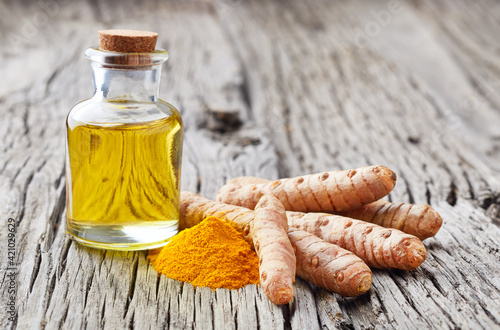 Fototapeta Turmeric root with curry powder and essential oil on old wooden background obraz