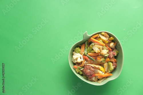 Fototapeta top view of homemade vegetable salad in bowl on green background  obraz