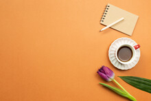 Notebook, Pencil, Cup Of Coffee, Tulip Flower On Orange Background. Work And Study Place. Flat Lay, Top View, Copy Space