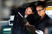 Hispanic Female Trainee Mechanics Working Underneath Car Together Car Maintenance And Auto Service Garage. Car Maintenance And Auto Service Garage Concept.
