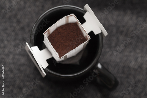 Carta da parati Drip coffee bag is in a black cup, top view, closeup