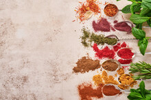 Colorful Herbs And Spices For Cooking: Turmeric, Dill, Paprika, Cinnamon, Saffron, Basil And Rosemary In A Spoon. Indian Spices. On Light Brown Stone Background. Top View.