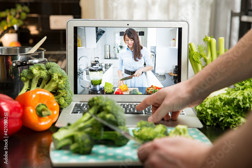 Fototapeta Beautiful happy woman streaming broadcast video blog about tasty and healthy food from home kitchen. Healthy lifestyle and social media. Man watching video recipe on laptop and cooking at home. obraz