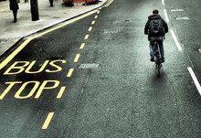 A Bus Stop Sign On The Road And A Cyclist On The Streets Of London.