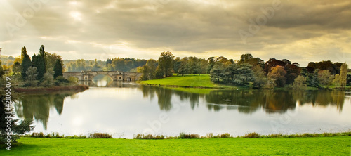 Fotografia tranquil sunset  in the Blenheim Palace lake and Vanbrugh Bridge in Oxfordshire,