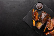 Smoked Beef Ribs With Bone And Barbecue Sauce On Black Slate Board, Top View, Copy Space. Roasted Beef Ribs.