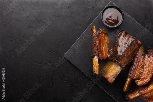 Fototapeta Smoked beef ribs with bone and barbecue sauce on black slate board, top view, copy space. Roasted beef ribs. obraz