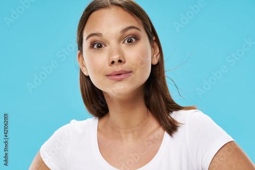 Slika na platnu Girl in a white T-shirt on a blue background close-up